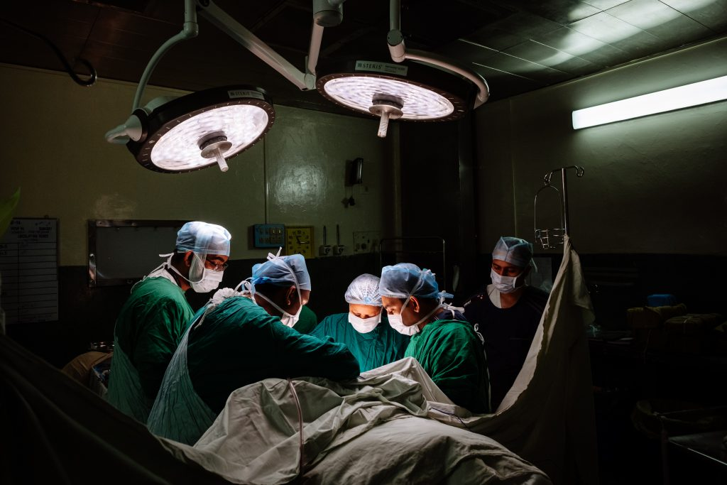 Photo shows surgical operation with 5 surgeons-nurses and one patient