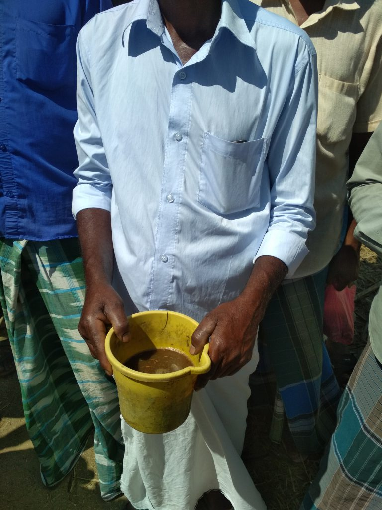 a man holds a jug filled with the home made organic manure