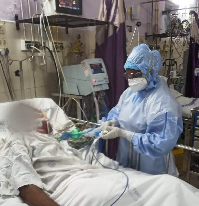 staff in ICU and full PPE tending to a patient