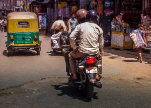 Motor bike in town shows both driver and passenger with helmet