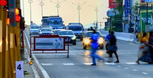 pedestrians cross a busy road with fast cars approaching as the light dims