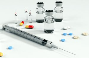 photo of various types of medicine. needle w syringe, ampoules, tablets and capsules
