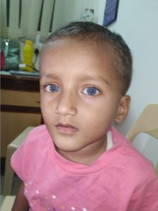 a young boy with blue eyes and Indian skin colouring