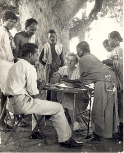 Dr Ida B Scuddder sits at a table under a tree with men and women around her