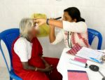 A docor checks the eyes of an old lady at the CONCH community clinic