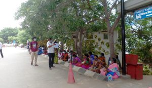 ladies sat on the path facing the road waiting for outpatient appointments at Chittoor
