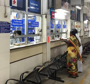 a row of counters in pharmacy with patients getting their medicines