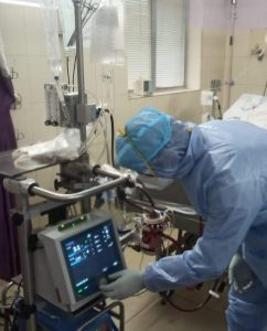 PPE equipment worn by a doctor in ICU monitoring the equipment of a patient