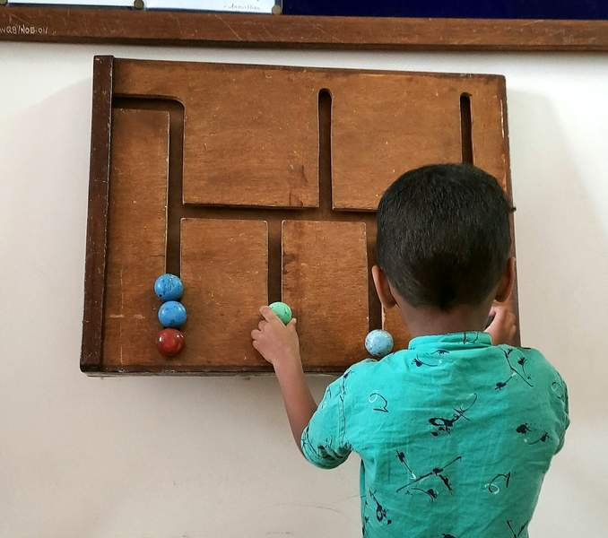 boy playing with puzzle on the wall