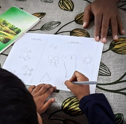 CHILD DRAWING WITH AN ADULT HAND holding the paper