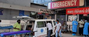 an ambulace draws up outside CMC emergency entrance with a COVID patient and staff wait to receive him